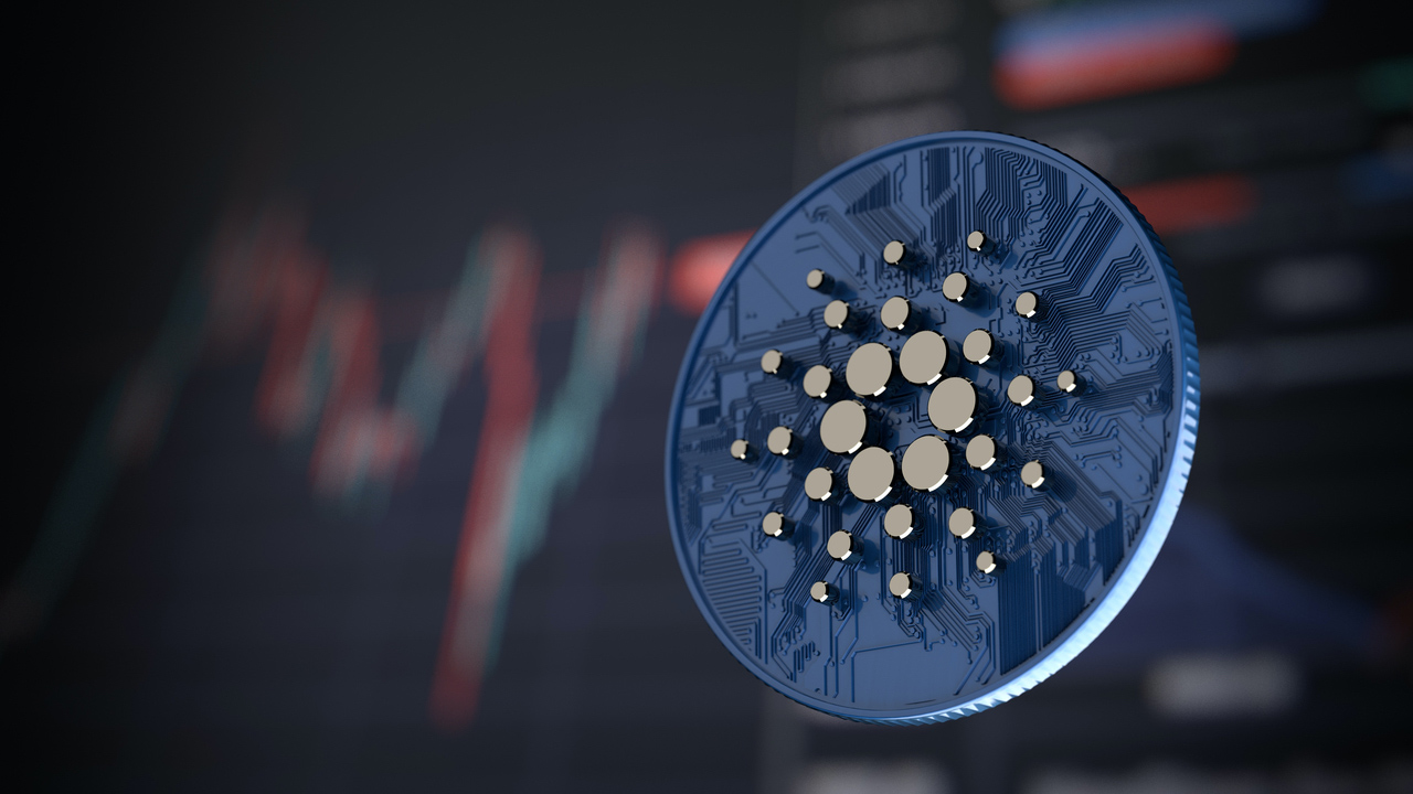 Picture of a Cardano coin in front of a market chart